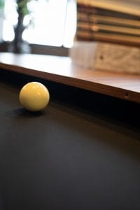 White Ball on Wood Table with Black Cloth-min