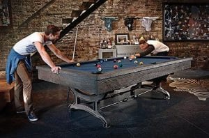 Two Men Playing Pool. One is watching, the other is taking a shot